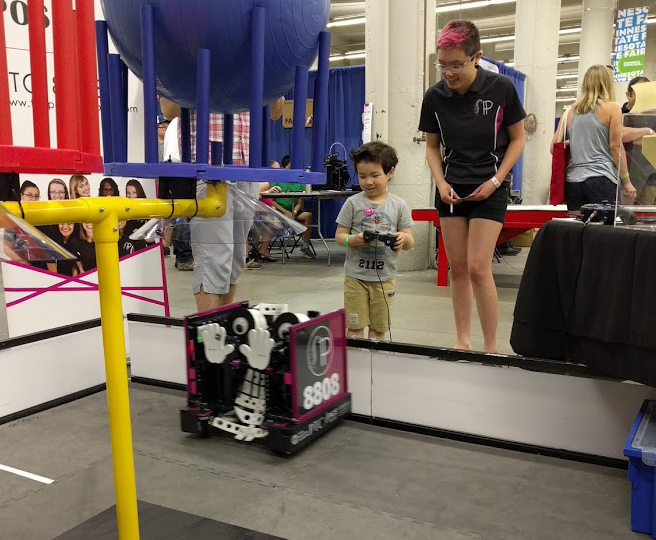 Young visitor happily driving the robot